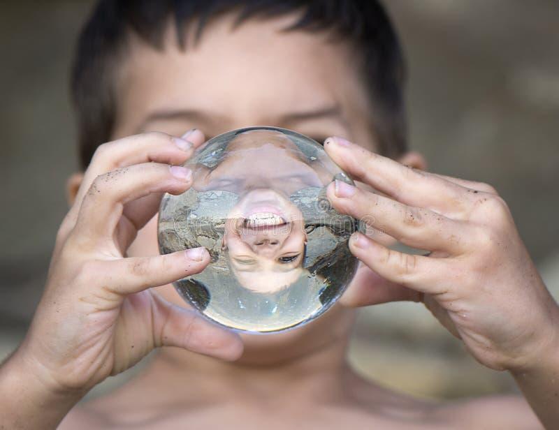 Het glimlachen gezicht in kristallen bol royalty-vrije stock afbeelding
