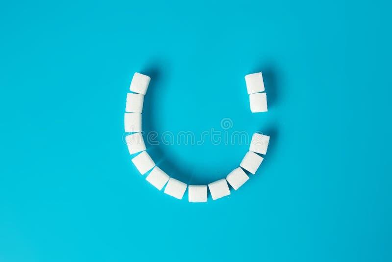 Het glimlachen gezicht met tandbederf van suikerkubussen wordt gemaakt op blauwe backgr die stock foto's