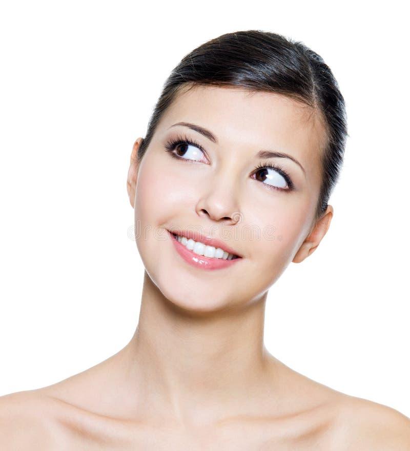 Het glimlachen gezicht van een jonge volwassen vrouw die omhoog kijkt stock afbeeldingen