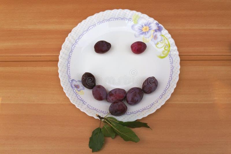 Het glimlachen gezicht van rijpe pruimen op een plaat stock afbeelding