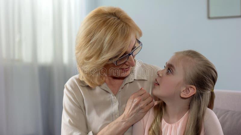 Het glimlachen grootmoeder het fluisteren geheim aan haar geschokte kleindochter, familie royalty-vrije stock foto's