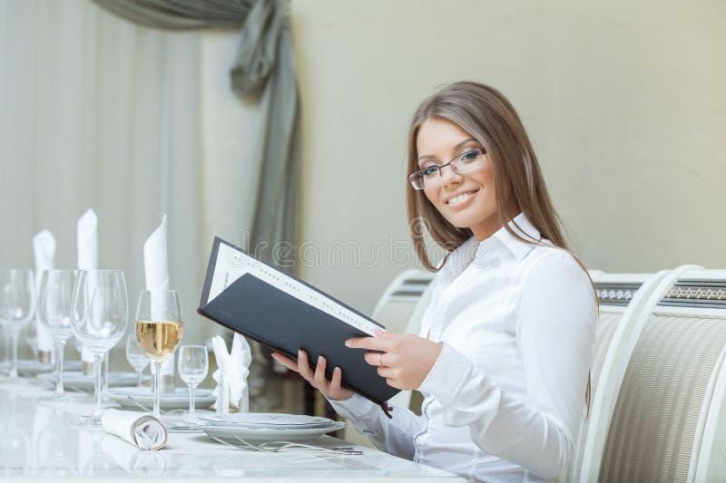 Het glimlachen het charmante vrouw stellen met menu, close-up stock foto