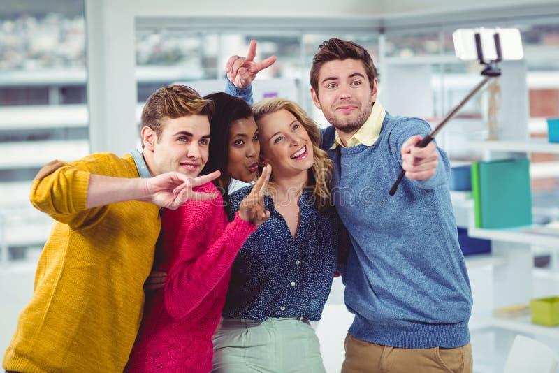 Het glimlachen het creatieve team stellen voor een selfie stock fotografie