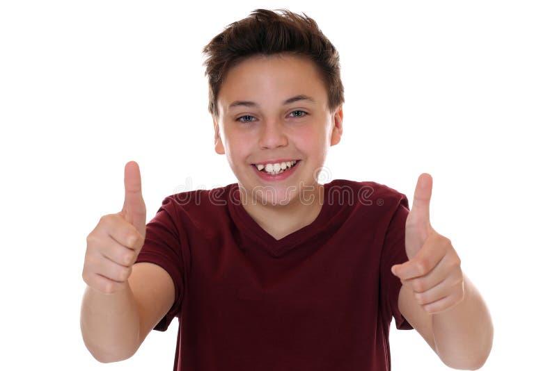 Het glimlachen het jonge tienerjongen omhoog beduimelt tonen royalty-vrije stock foto's