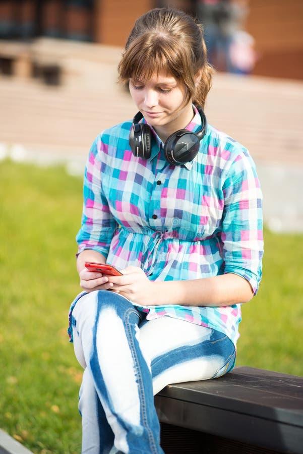 Het glimlachen het jonge universiteitsmeisje texting op een celtelefoon campus royalty-vrije stock foto's