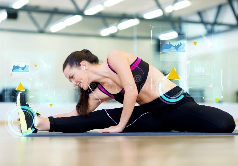 Het glimlachen het jonge vrouw uitrekken zich op mat in gymnastiek stock afbeeldingen