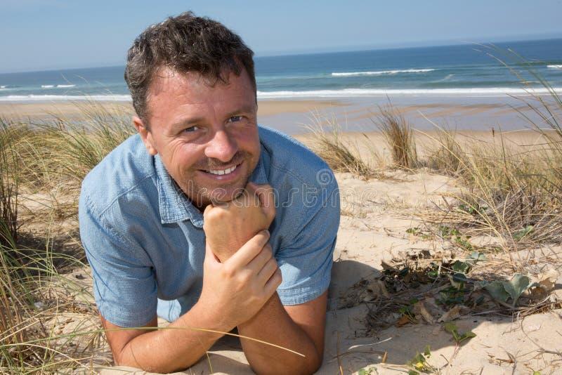 Het glimlachen het knappe mens ontspannen op het strand die op zand liggen royalty-vrije stock fotografie