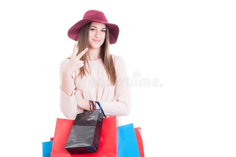 Het glimlachen het leuke meisje ontspannen bij het winkelen en het doen van vredesgebaar royalty-vrije stock afbeeldingen