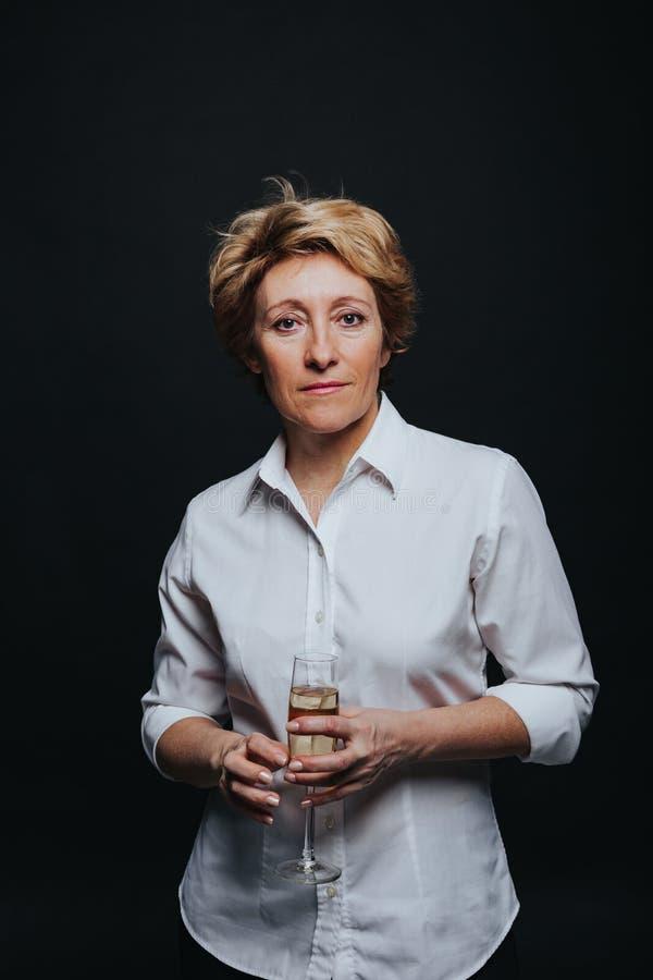 Het glimlachen het midden oude vrouw stellen met champagne stock foto