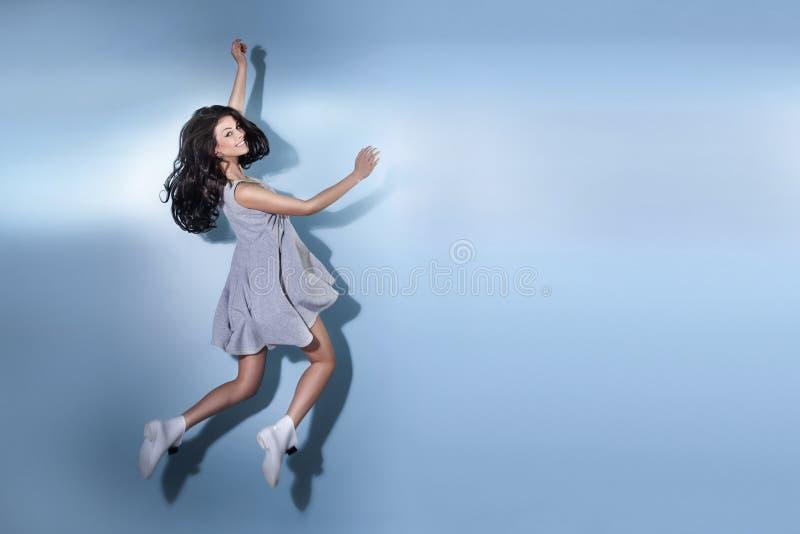 Het glimlachen het mooie donkerbruine vrouw springen stock foto's