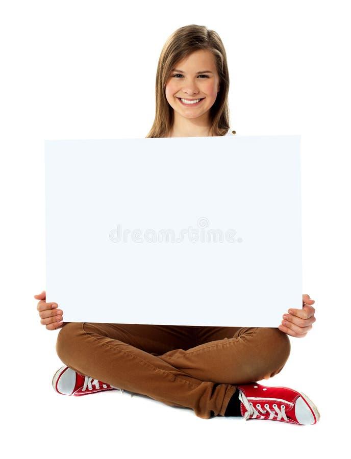 Het glimlachen het mooie tiener stellen met leeg aanplakbiljet royalty-vrije stock afbeelding