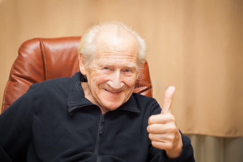 Het glimlachen het oude mens omhoog beduimelt tonen stock foto's
