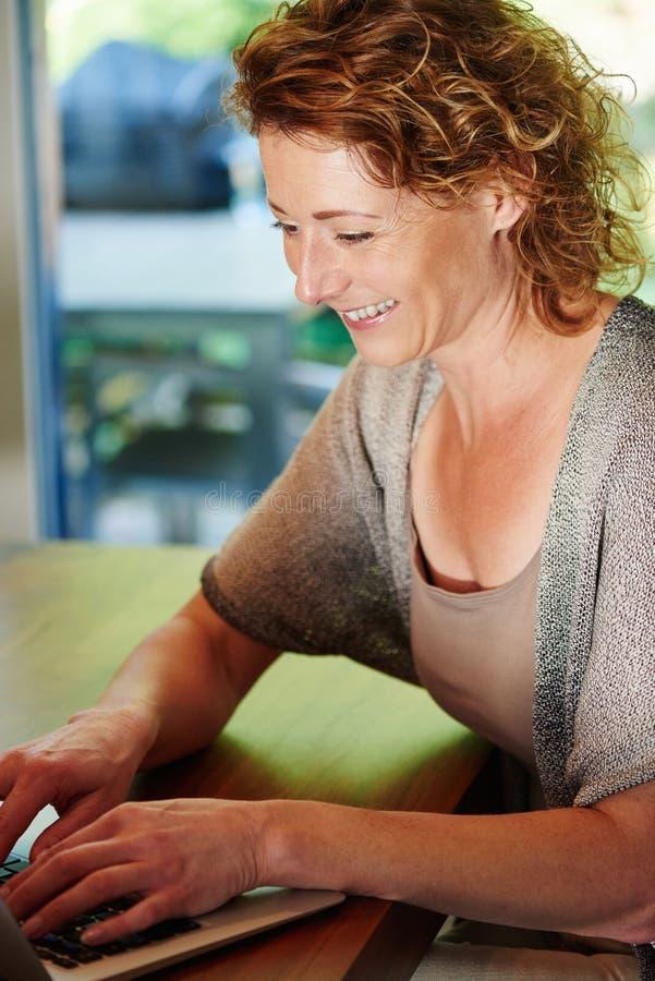 Het glimlachen het oudere vrouw typen op laptop bij bureau royalty-vrije stock fotografie