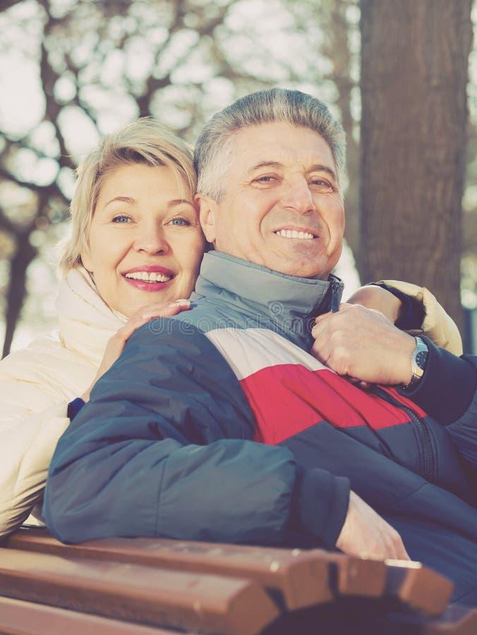 Het glimlachen het rijpe paar ontspannen in park stock afbeelding