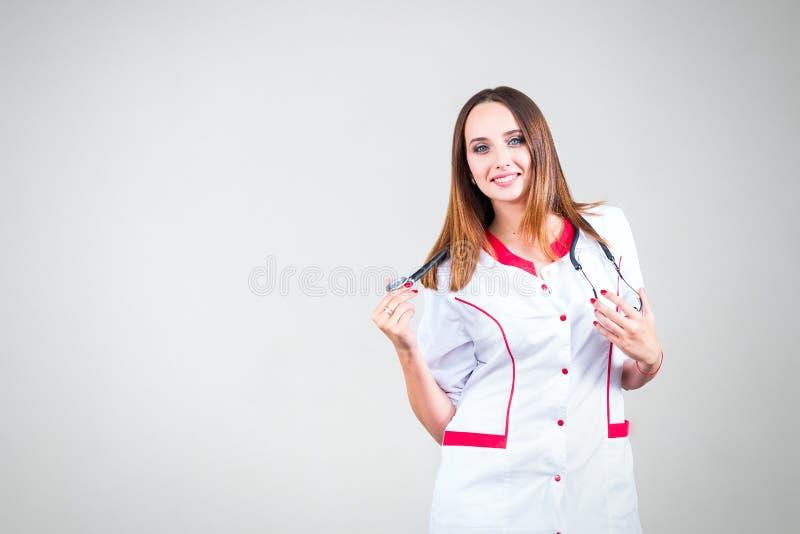 Het glimlachen het vrouwelijke arts stellen met laboratoriumlaag en stethoscoopisola stock afbeelding