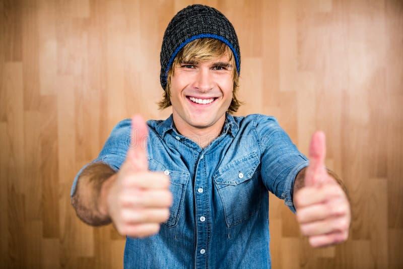 Het glimlachen hipster met omhoog duimen stock fotografie