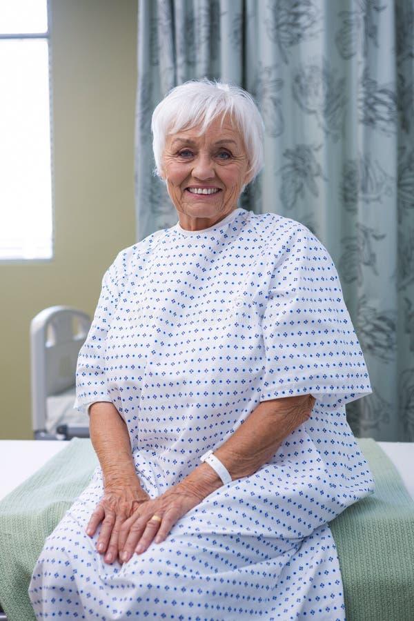 Het glimlachen hogere geduldige zitting op bed in het ziekenhuis royalty-vrije stock afbeelding