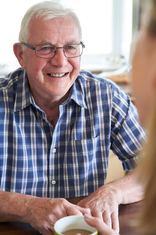 Het glimlachen Hogere Man Zitting in Keuken die met Vrouw thuis spreken royalty-vrije stock foto's