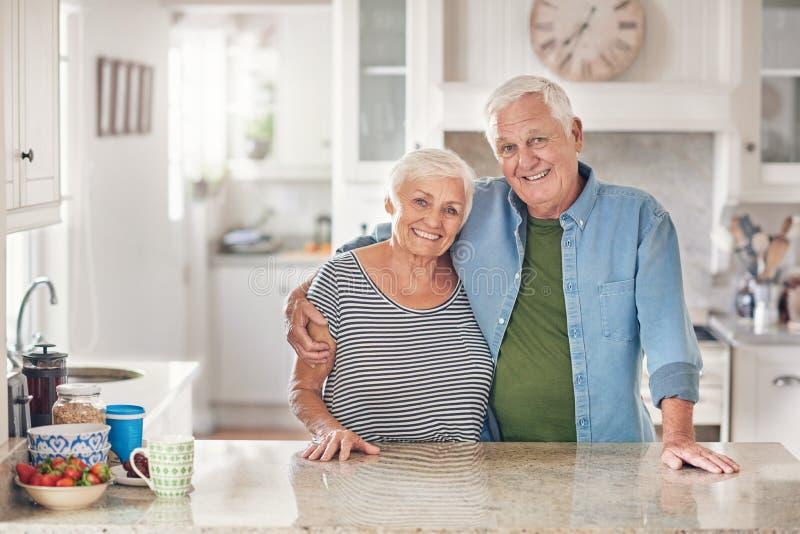 Het glimlachen hogere paarinhoud thuis in hun keuken stock fotografie