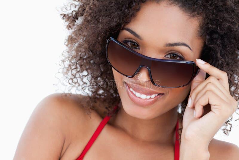 Het glimlachen jong brunette die over haar zonnebril kijken stock afbeeldingen