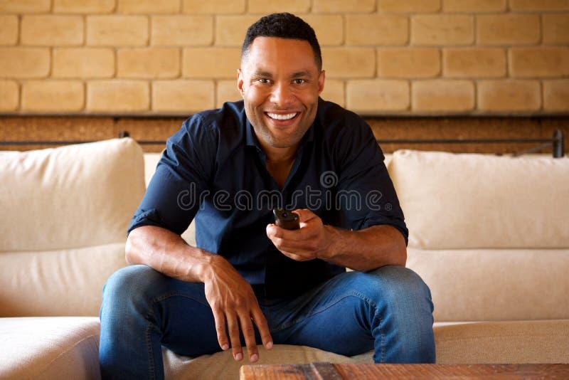 Het glimlachen jonge Afrikaanse Amerikaanse mensenzitting op bank en het letten op TV stock afbeelding