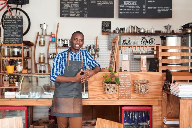 Het glimlachen jonge Afrikaanse barista die op een koffieteller leunen royalty-vrije stock fotografie