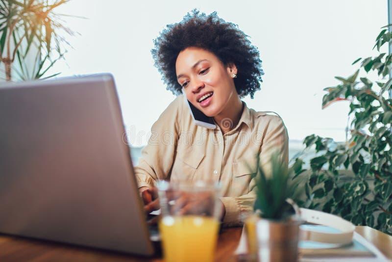 Het glimlachen jonge Afrikaanse vrouwelijke ondernemerszitting bij een bureau in haar huisbureau die online werken stock fotografie