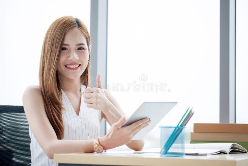 Het glimlachen het jonge Aziatische bedrijfsvrouw toont werken met tablet aan bureau en duim in een modern bureau stock foto