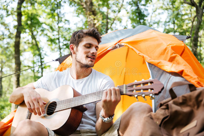 Het glimlachen jonge mensentoerist zitting en het spelen gitaar in bos stock foto