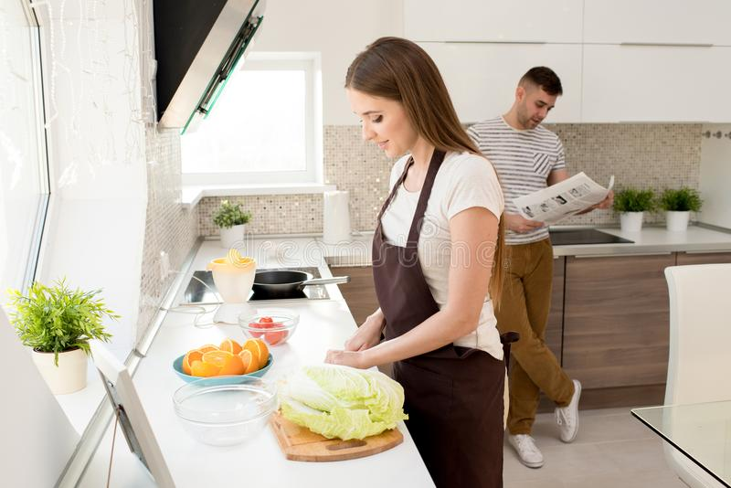 Het glimlachen het jonge vrouw koken voor echtgenoot thuis royalty-vrije stock afbeeldingen