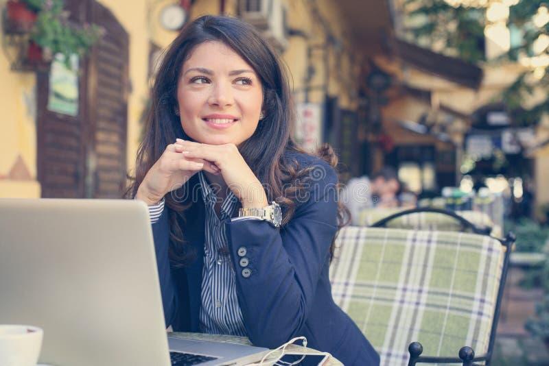 Het glimlachen jonge vrouw het luisteren muziek bij koffie stock afbeelding
