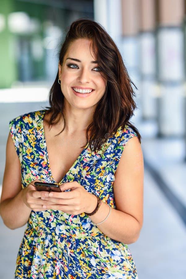 Het glimlachen het jonge vrouw typen in slimme telefoon in openlucht royalty-vrije stock afbeelding