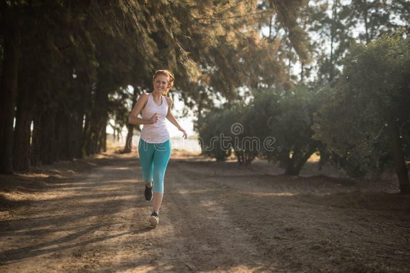 Het glimlachen jonge vrouwenjogging bij de landweg tijdens zonnige dag stock afbeelding