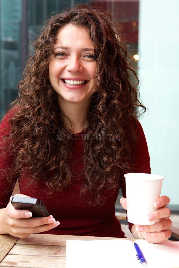 Het glimlachen jonge vrouwenzitting bij koffie stock foto