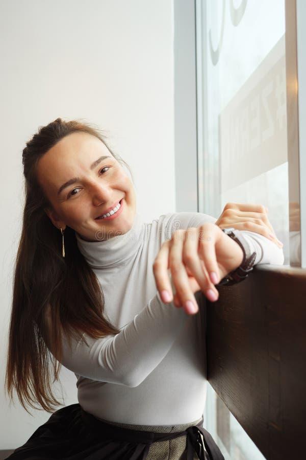 Het glimlachen jonge vrouwenzitting bij koffie en het bekijken camera stock afbeelding