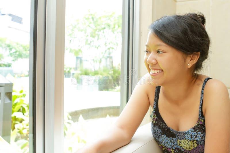 Het glimlachen jonge vrouwenzitting door het venster royalty-vrije stock afbeelding