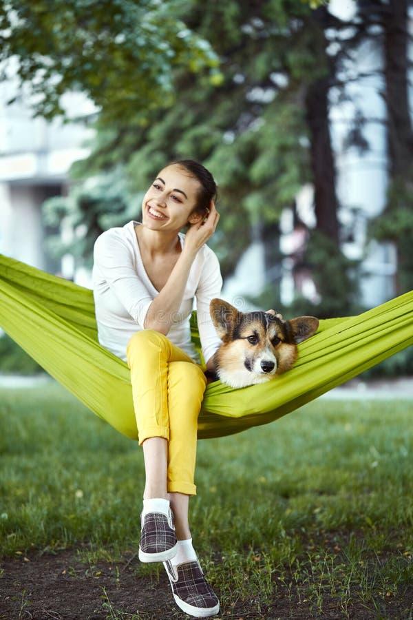 Het glimlachen jonge vrouwenzitting in groene hangmat met leuke hond Welse Corgi in een park in openlucht Mooi gelukkig wijfje bi stock afbeelding