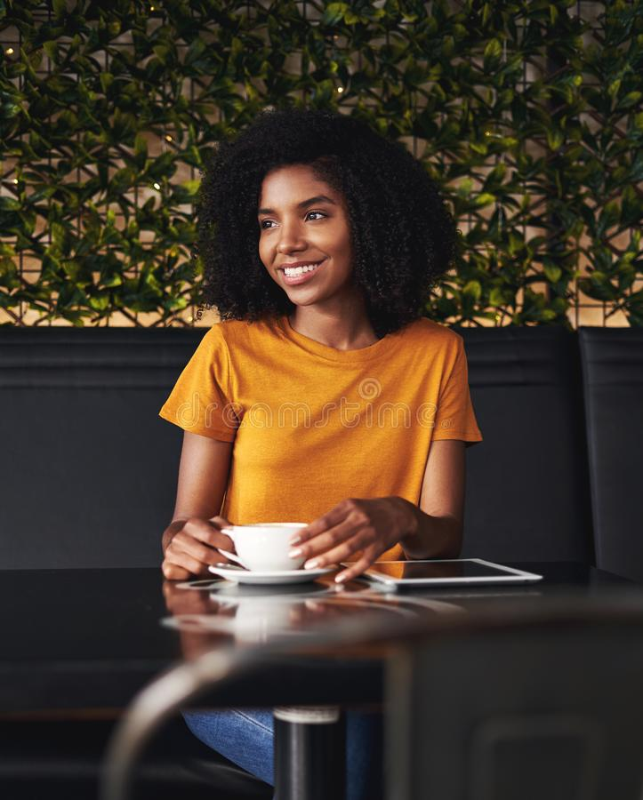Het glimlachen jonge vrouwenzitting in koffie stock foto's