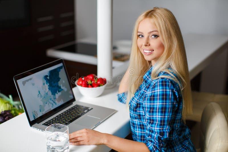 Het glimlachen jonge vrouwenzitting met laptop royalty-vrije stock afbeelding