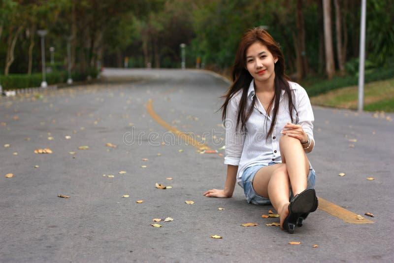 Het glimlachen jonge vrouwenzitting op asfaltweg zij gelukkige en echte ` s royalty-vrije stock foto