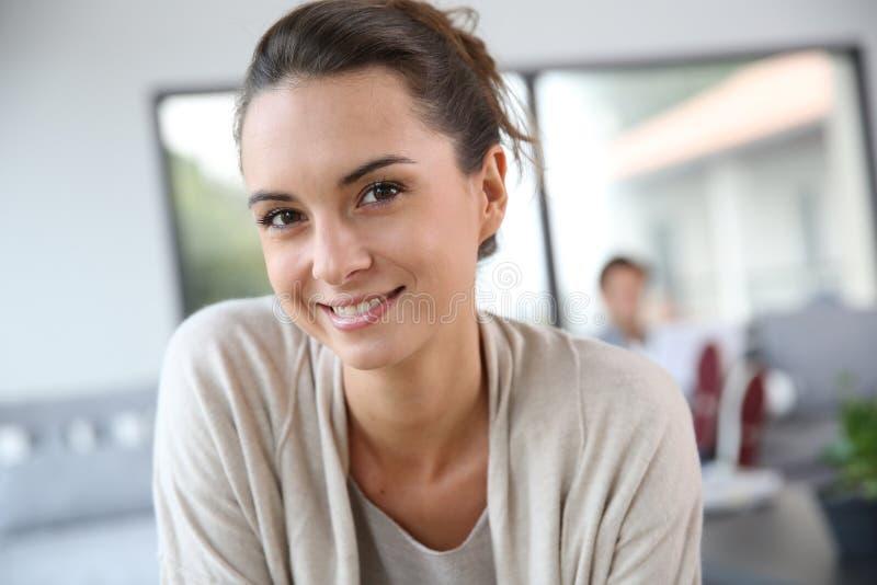 Het glimlachen jonge vrouwenzitting thuis royalty-vrije stock fotografie