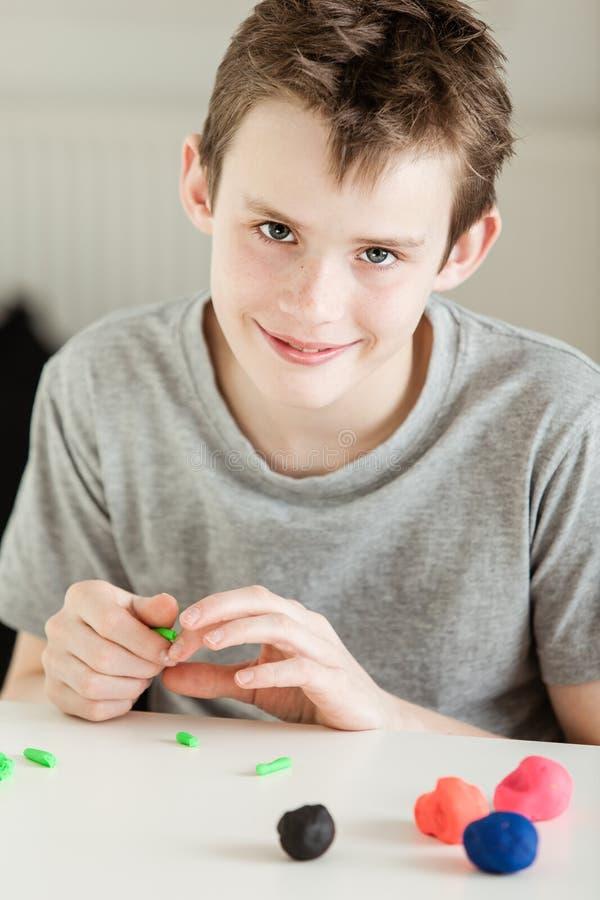Het glimlachen jongen het spelen met klei op lijst royalty-vrije stock fotografie