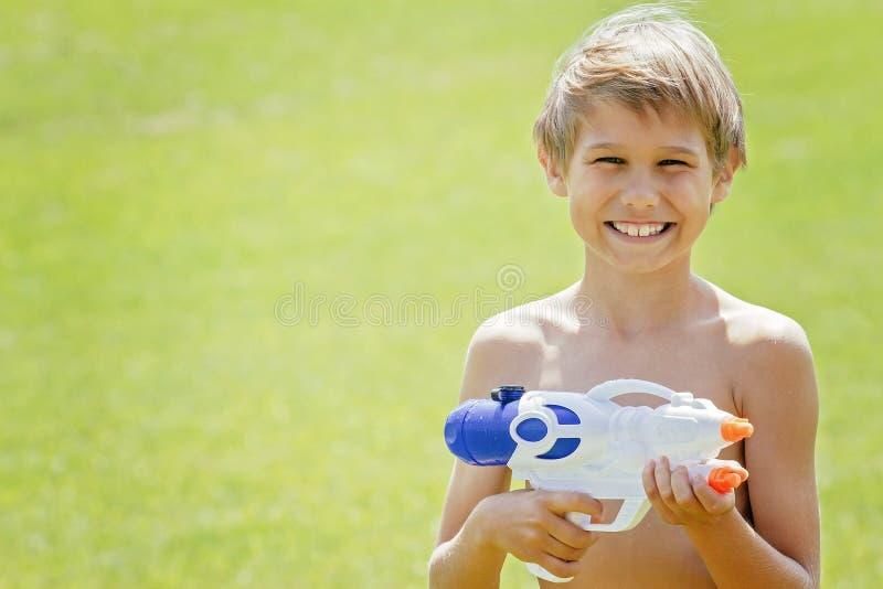 Het glimlachen jongen het spelen met waterkanon bij de zomerdag stock afbeeldingen