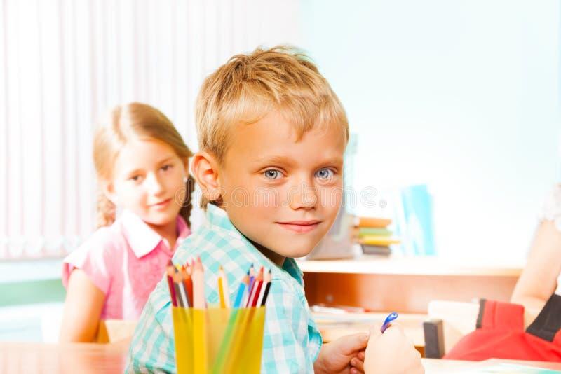 Het glimlachen jongenszitting bij bureau met meisjesklasgenoot stock fotografie