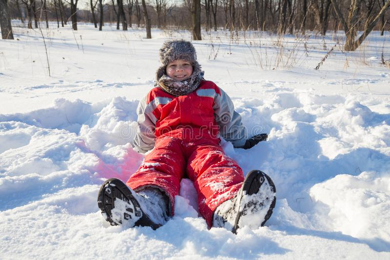 Het glimlachen jongenszitting bij de sneeuw op park stock afbeeldingen