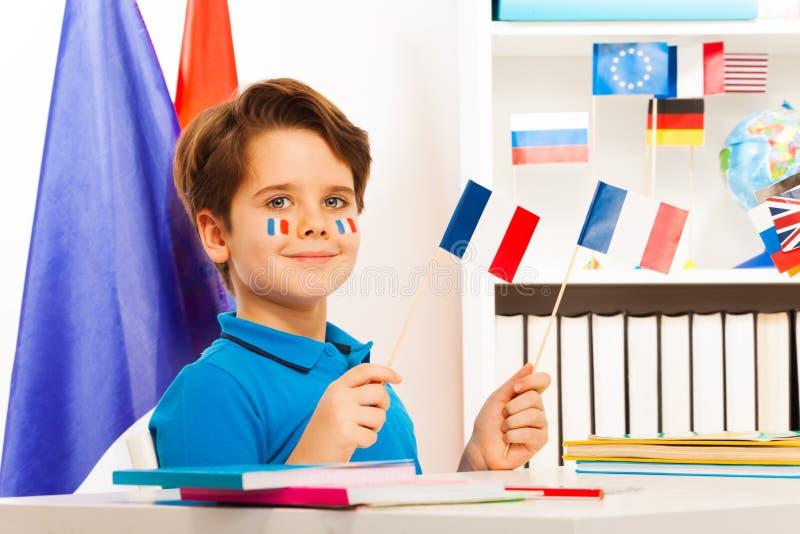 Het glimlachen jongenszitting die bij bureau Franse vlaggen houden stock foto's