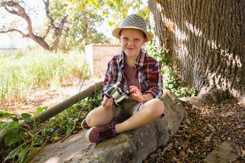 Het glimlachen jongenszitting op de rots met verrekijkers royalty-vrije stock afbeeldingen
