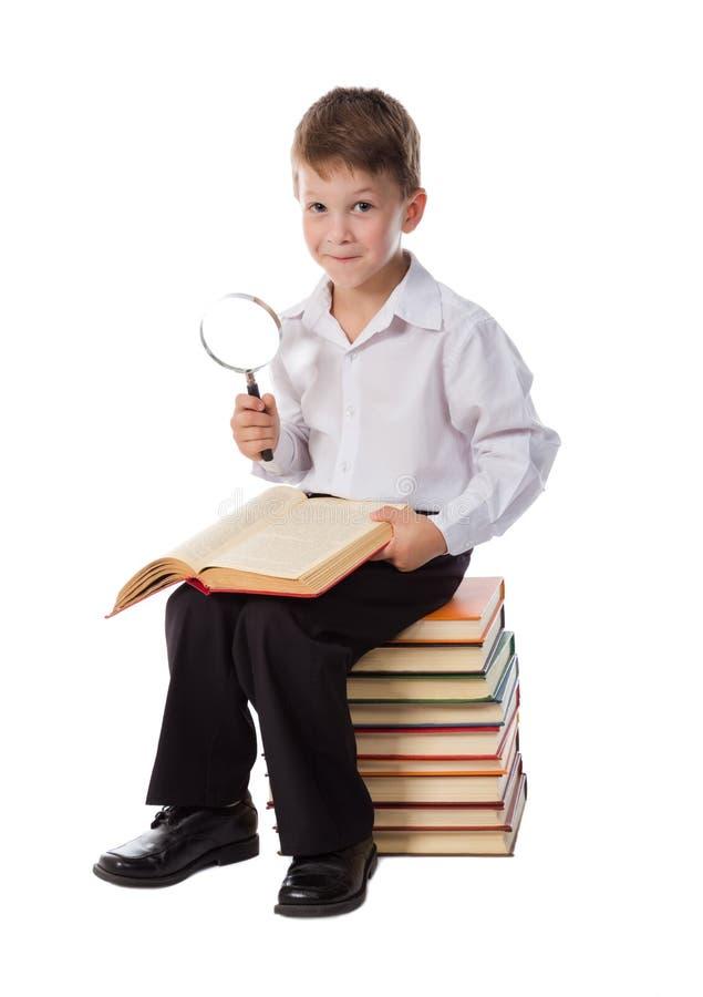Het glimlachen jongenszitting op stapel van boeken royalty-vrije stock afbeelding