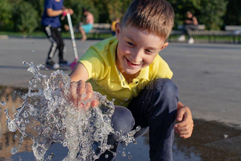 Het glimlachen het Kaukasische jongen spelen met fonteinwater in stadspark royalty-vrije stock afbeeldingen