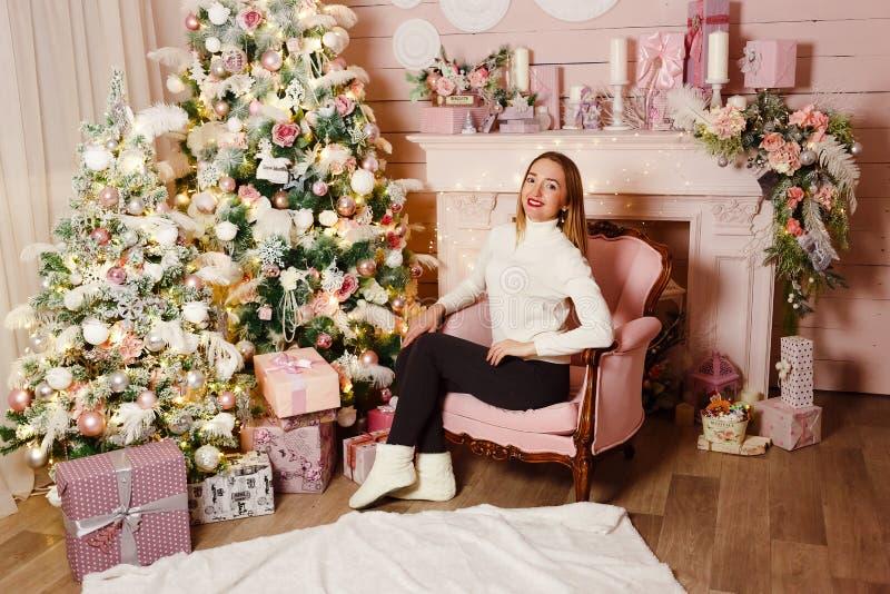 Het glimlachen Kaukasische vrouwenzitting als voorzitter dichtbij de Kerstboom royalty-vrije stock afbeelding